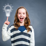 Cute surprised girl pointing at light bulb. Stock Images