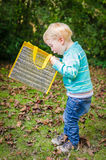 Cute surprised little blond boy looking inside bag outdoor Royalty Free Stock Images