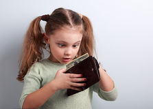 Cute surprising kid girl holding and looking in wallet with doll. Ars with open mouth and think how can to spend so much money. Happy childhood royalty free stock images