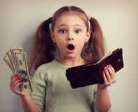 Cute surprising kid girl holding wallet and dollars with open mo Stock Photography