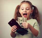 Cute surprising kid girl holding wallet and looking on dollars w Royalty Free Stock Image