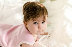 Cute sweet little baby girl looking at camera and lying on bed Royalty Free Stock Images