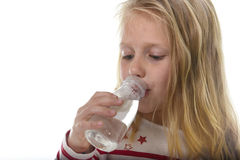 Cute sweet little girl with blue eyes and blond hair 7 years old holding bottle of water drinking Stock Photos