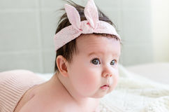 Cute sweet little newborn baby girl looking with curiosity side-face Royalty Free Stock Image