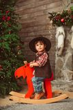 Little boy on rocking horse in Christmas interior royalty free stock images