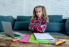 Cute sweet sad and overwhelmed blonde hair primary school girl looking angry bored and tired in stress with homework and studying. With books and computer at stock image