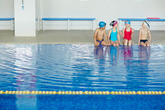 Cute swimmers. Group of kids in swimwear talking in swimming pool Royalty Free Stock Image