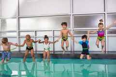 Cute swimming class jumping in the pool. At the leisure center Royalty Free Stock Photography