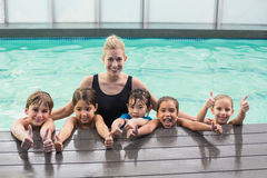 Cute swimming class in pool with coach Royalty Free Stock Photo