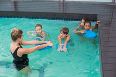 Cute swimming class in pool with coach Royalty Free Stock Images