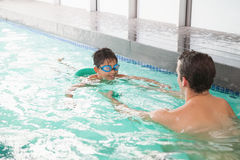 Cute swimming class in pool with coach Stock Photos