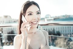 Cute talkative woman smiling and holding cellphone near head. Royalty Free Stock Photography