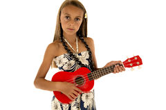 Cute tan girl wearing tropical dress playing ukulele Royalty Free Stock Image