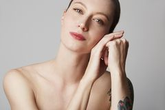 Cute tattooed redhead woman with bare shoulders holds her hand near the face over gray background. Cosmetology and skin. Care concept stock image