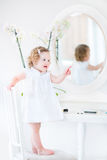 Cute tddler girl in white dress playing at white mirror Stock Photos