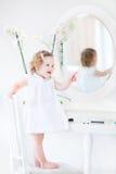 Cute tddler girl in white dress playing at white mirror Stock Photos