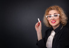 Cute teacher with chalk in front of blackboard Stock Photos