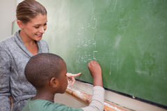 Cute teacher and a pupil making an addition Royalty Free Stock Photos