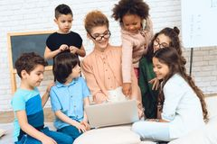 Cute teacher sits with school children who have surrounded her and are looking at laptop. Stock Photo