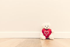 Cute teddy bear with big red plush heart. Sitting on wooden floor against white wall. Stock Image