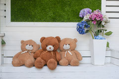 Cute teddy bear brown soft hair. Teddy bear sitting beside a flower vase Stock Photos