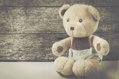 Cute teddy bear on brown wooden Royalty Free Stock Images