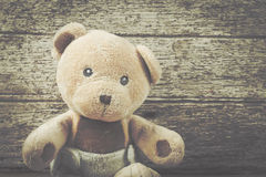 Cute teddy bear on brown wooden Royalty Free Stock Photos