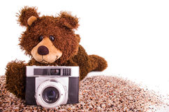 Cute teddy bear is with a camera on the sand Stock Photo