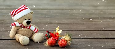 Cute teddy bear with a Christmas red balls on a wooden background, copy space. Banner, snow texture stock photos