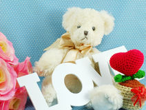 Cute teddy bear concept valentine day on blue polka dot background and artificial rose flower Stock Photo