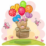 Cute Teddy Bear girl with balloons. Cute Teddy Bear girl in the box is flying on balloons Royalty Free Stock Photography