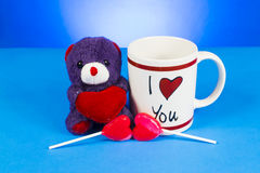 Cute teddy bear holding out a heart sitting next ot an Stock Photo