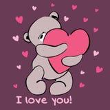 Cute teddy bear hugging a heart. Royalty Free Stock Photos