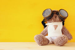 cute teddy bear with pilot glasses on wooden table Royalty Free Stock Photos