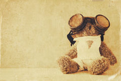 cute teddy bear with pilot glasses on wooden table Royalty Free Stock Photo