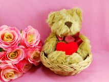 Cute teddy bear with red heart in the basket with pink background Royalty Free Stock Photo