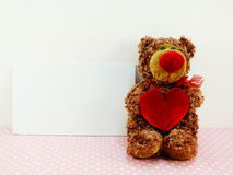 Cute teddy bear with red heart on pink background Stock Images
