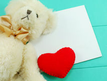 Cute teddy bear with red heart valentines day on green backgroun Royalty Free Stock Image
