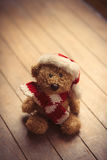 Cute teddy bear in santa claus hat on the wonderful brown wooden Stock Photo