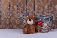 Cute teddy bear is sitting with gift heart of candy. Stock Photo