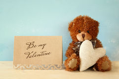 Cute teddy bear sitting and holding a heart Stock Photography