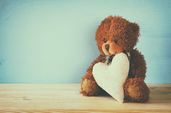 Cute teddy bear sitting and holding a heart Stock Photo