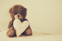Cute teddy bear sitting and holding a heart Royalty Free Stock Photo