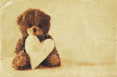 Cute teddy bear sitting and holding a heart Royalty Free Stock Image
