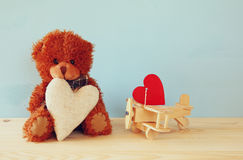 Cute teddy bear sitting and holding a heart Royalty Free Stock Images