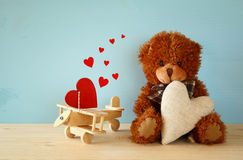 Cute teddy bear sitting and holding a heart Stock Images