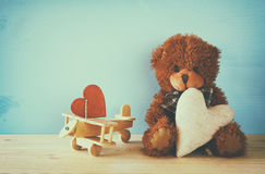 Cute teddy bear sitting and holding a heart Royalty Free Stock Photography