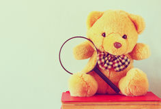 Cute teddy bear sitting over stack of books Stock Photography