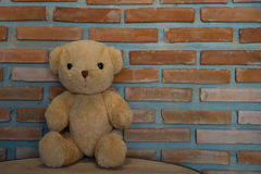 Cute teddy bear sitting on wooden floor against brick wall backg Royalty Free Stock Image