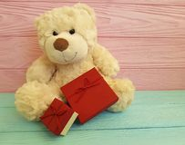 Cute teddy bear toy with red box  pink and blue wooden Stock Photo